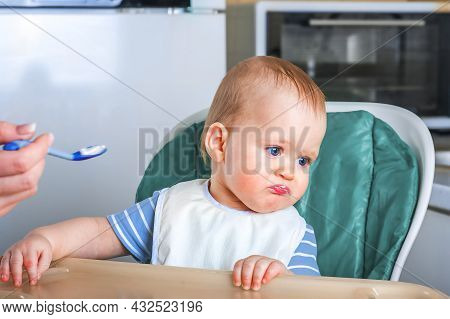 Llittle Baby Does Not Want To Eat First Complementary Food. Disgruntled Child At Highchair.