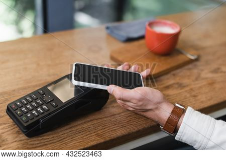 Partial View Of Man Paying With Smartphone In Cafe