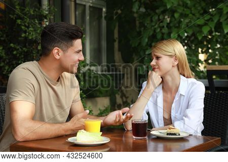 Young Woman Having Boring Date With Talkative Man In Outdoor Cafe