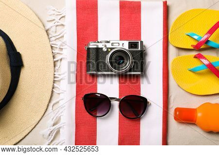 Hat, Sunglasses, Camera, Sunscreen, Beach Towel And Flip Flops On Sand, Flat Lay
