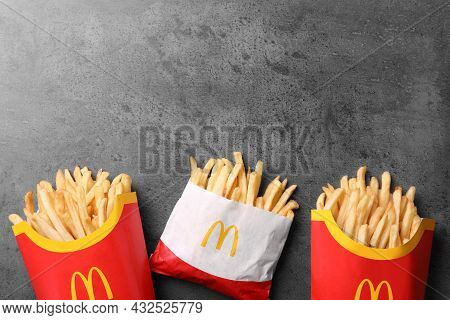Mykolaiv, Ukraine - August 12, 2021: Small And Big Portions Of Mcdonald's French Fries On Grey Table