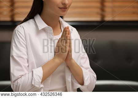 Religious Woman With Clasped Hands Praying Indoors, Closeup