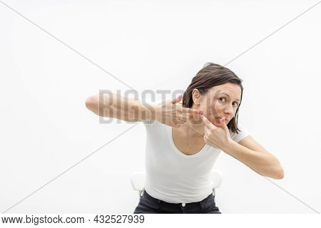 Photo Of Woman With Acne Problem Squeezing Pimple Indoors.