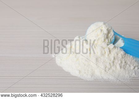 Powdered Infant Formula And Scoop On White Wooden Table, Closeup With Space For Text. Baby Milk