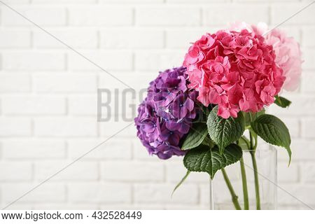 Vase With Beautiful Hortensia Flowers Near White Brick Wall. Space For Text