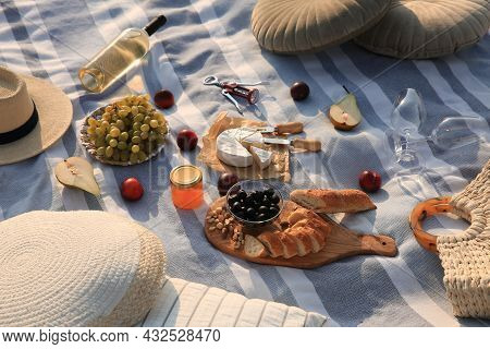 Different Tasty Snacks And Wine On Picnic Blanket Outdoors