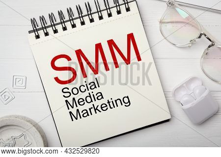Notebook With Text Smm (social Media Marketing), Eyeglasses And Earphones On White Wooden Table, Fla