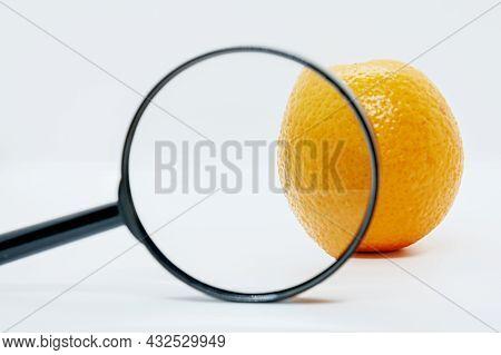 Close-up Of Orange Under Magnifying Glass. Orange Peel Rough For Symbolize Of Skin. Anti-cellulite C