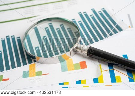 Magnifying Glass On Charts Graphs Paper. Financial Development, Banking Account, Statistics, Investm