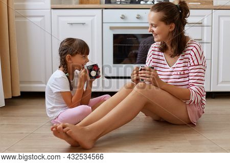 Full Length View Of Happy Mother Drinking Tea From Cups With Her Smiling Daughter, Family Sitting On