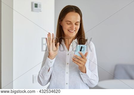 Portrait Of Smiling Dark Haired Young Adult Female Wearing White Shirt Standing At Home With Phone I