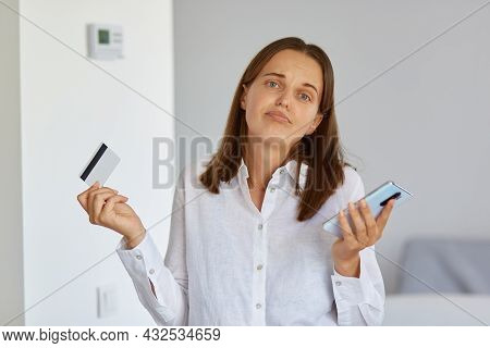 Portrait Of Puzzled Female With Dark Hair Standing With Cell Phone And Credit Card In Hands, Shruggi