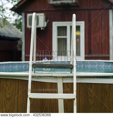An Above Ground Swimming Pool Ladder And A House In The Background, Daylight Shot