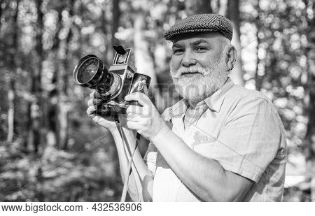 Old Photographer Use Retro Camera. Senior Man Relax In Summer Nature. Bearded Man Holding Retro Came