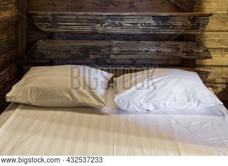 Bedroom Interior Evening. Fragment Of Wooden Double Bed With Mattress, Pillows And Sheet. Walls Of R