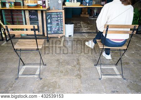 Customer Waiting For Her Coffee In Coffee Shop While Keep Spaced Between Each Chairs Make Separate F
