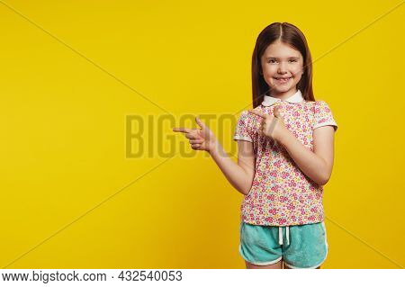 Caucasian Girl Kid, Points Away With Both Forefingers, Shows Blank Space For Your Promotion, Isolate