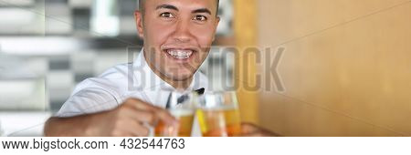 Portrait Of Young Man Holding Glass Of Beer While Clinking Glasses With Another Glass