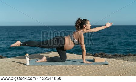 Young Pregnant Woman Doing Prenatal Pilates Exercises Session Next The Sea - Health Lifestyle And Ma