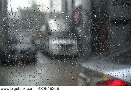 Raindrops Run Down On Car Windshield From Inside View. Traffic Jam During The Heavy Rain Storm