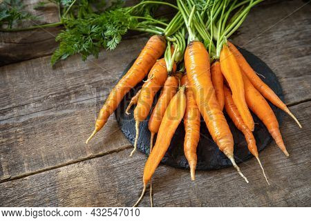 Healthy Ripe Juicy Carrots On A Wooden Kitchen Table. The Concept Of Organic Nutrition And Autumn Ha