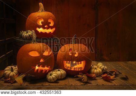 Silly And Scary Carved Pumpkins Lit Inside A Barn For Halloween.