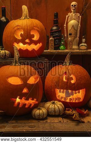 Silly And Scary Carved Lit Pumpkins  With Bottles Of Potions For Halloween.