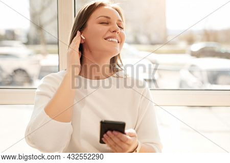 Happy Young Female With Smartphone Adjusting Tws Earbuds While Enjoying Favorite Songs As Standing N