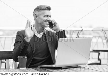 Happy Businessman Give Hand Salute Gesture Talking On Mobile Phone In Internet Cafe Outdoors, Greeti