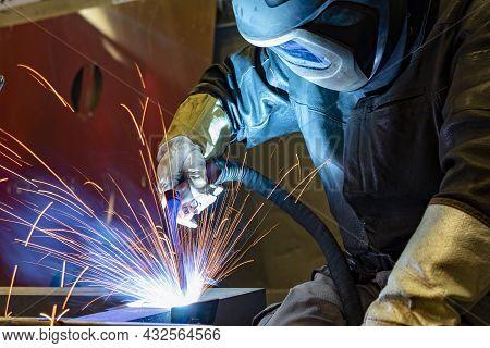Welder With Protective Mask Welding Metal And Sparks. Industrial Steel Welder In Factory.