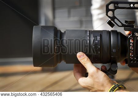 Hand Holds A Long Camera Lens Close-up Of The Photographer