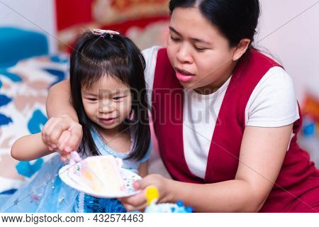 Mother And Daughter Are Helping To Put Cakes On Plates, Celebrating A Cute Little Girl's Birthday In