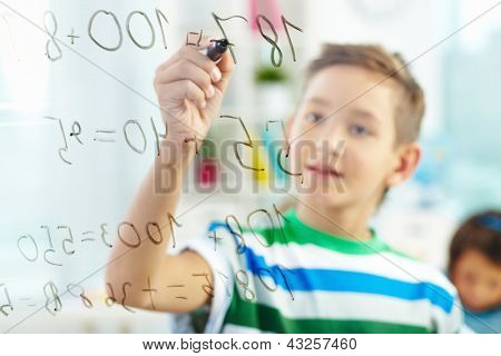 Cute learner doing sums with schoolmate on background