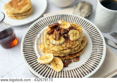 Protein Pancakes Topped With Banana, Syrup And Glazed Pecans. Healthy Diet Flapjacks.