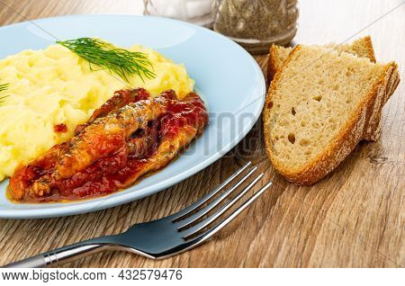 Canned Sprats In Tomato Sauce With Mashed Potato And Dill In Blue Glass Plate, Pepper And Salt, Slic