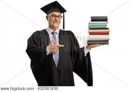 Mature man in a graduation gown holding a pile of books and pointing isolated on white background