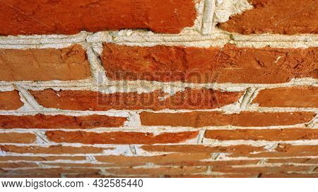 Bright Red Brick Wall With White Rough Seams In A Corner Perspective View, Background Of Old Tilted