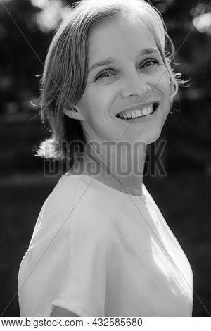 Portrait Of Happy Mid Adult Woman Smiling At Camera. Happy Face Of Attractive Lady Posing Outdoors.