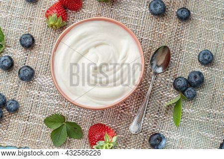 Ceramic bowl with plain yoghurt and berries on the table. Light summer mood.