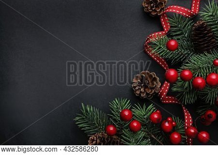 Christmas design on black background. christmas tree branches background. red ornaments, fir tree branches and pine cones