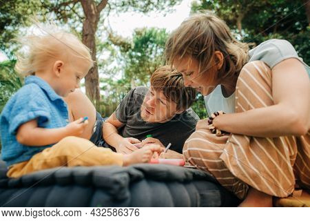 Portrait Of Smiling Couple Painting With Child Outdoors. Mid Adult Parents Resting On Mattress With