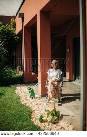 Relaxed Mid Adult Woman Resting On Backyard. Lady Wearing Sunglasses Sitting In Chair At Her House E