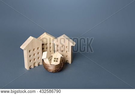 Small Houses In A Birds Nest Are Surrounded By Large Buildings. Residential Buildings And Houses In