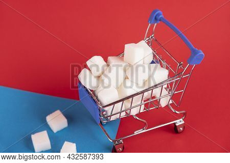 A Shopper's Cart Is Filled With Refined Sugar Cubes On A Red Background. Copy Space.