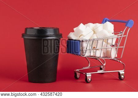 A Shopper's Cart Is Filled With Refined Sugar Cubes And A Black Paper Cup For Coffee Or Tea On A Red