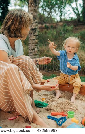 Cute Little Girl Playing In Sandbox With Toys, Her Mother Sitting By Her. Woman Resting With Her Chi