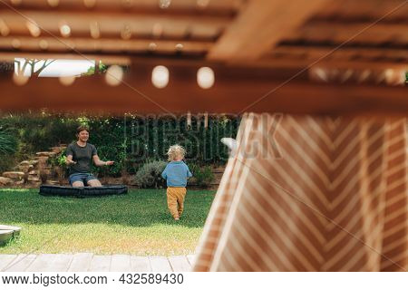 Little Girl Running To Her Father On Backyard, Her Mother Standing At Table Outdoors. Happy Man Rest