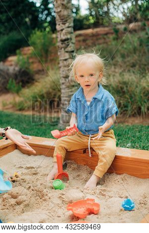 Portrait Of Joyful Little Child Playing In Sandbox. Cute Toddler Girl Playing With Sand On Playgroun