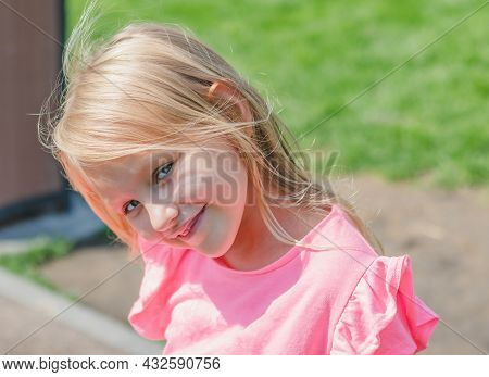 Portrait Of A Cute Pretty Girl 6-7 Years Old, Blonde In A Pink Blouse, With A Charming Smile