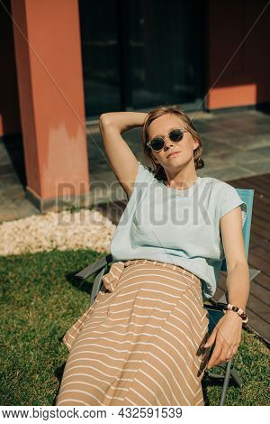Portrait Of Relaxed Woman Sitting On Chair Outdoors. Mid Adult Lady Wearing Sunglasses Resting At He